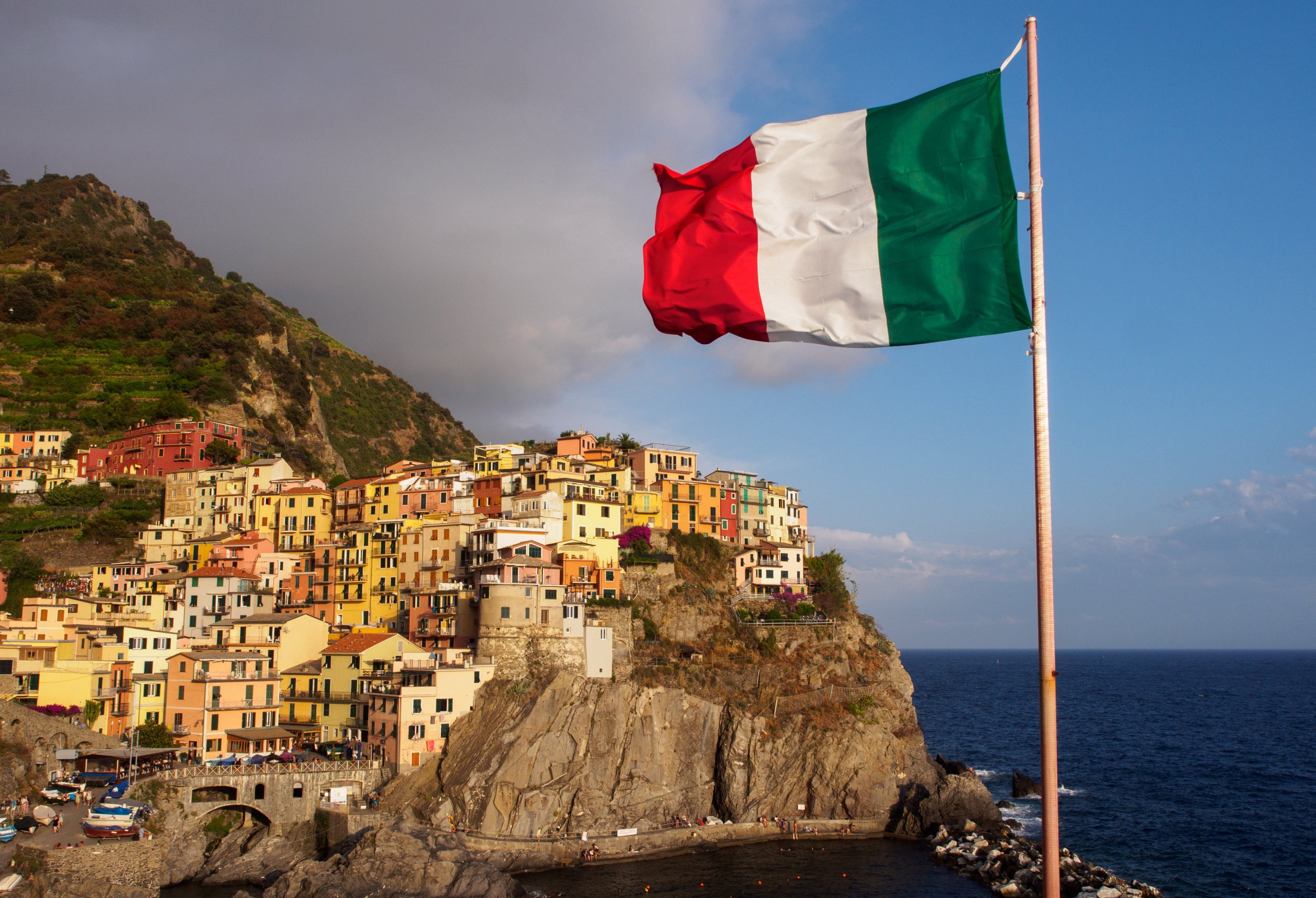 Manarola village in Cinque Terre with italian flag in foreground