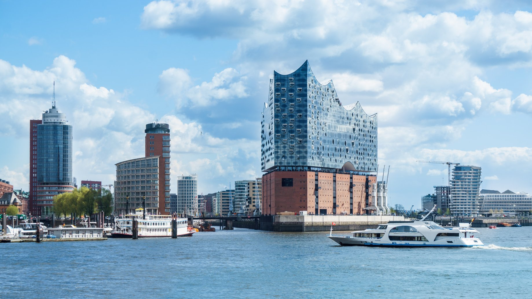 Hamburg, elbphilharmonie and modern buildings with boat to the harbor tour
